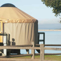 traditional yurt tent in front of lake