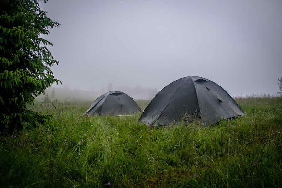 two tents in a grassy field in the rain